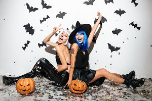 Two cheerful young women in leather halloween costumes