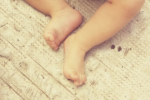 Baby feet sitting on metal texture