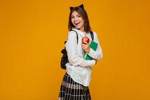 Portrait of a happy pretty schoolgirl holding books