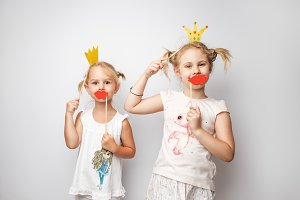 Two cute little girls with paper crown and red lips posing white background at home.