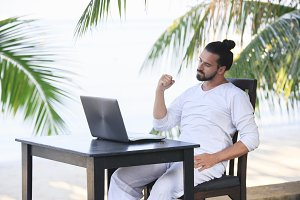 Man relaxing on the beach with laptop, freelancer show win