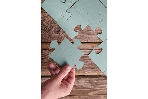Incomplete puzzles lying on wooden rustic boards.
