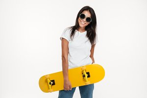 Portrait of a happy cheerful woman holding skateboard