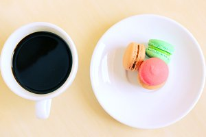 Colorful macarons and cup of coffee