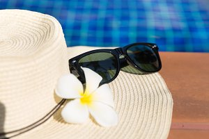 straw hat sunglasses near pool