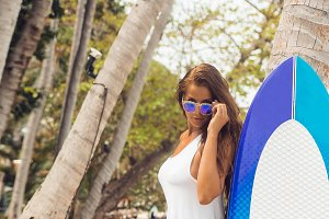 Pretty girl with surf board on beach