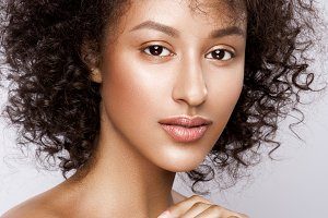 Fashion studio portrait of beautiful african american woman with perfect smooth glowing mulatto skin, make up