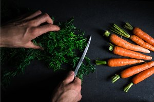 Cutting green carrot leaves and carrots