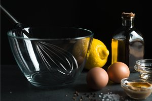 Eggs, olive oil, mustard on a black background