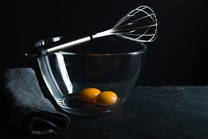 Chicken yolks in a glass bowl and whisk for whipping