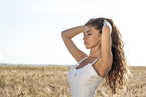 Beautiful summer girl in a wheat field, in a white dress, tanned skin, happy on vacation in the fresh air. A sunny day. happiness, nature, summer holidays, vacation and people concept