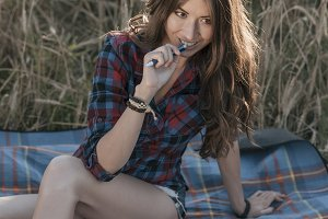 Girl sitting in a field shirt, wheat relaxing in nature, beautiful brunette hair. Keeps notepad pnany for the future. After the lessons, he writes the assignment. The concept notes are lessons for the interview.
