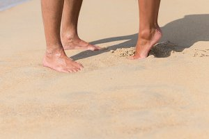 Legs of kissing couple on beach
