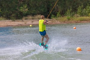 Man riding wakeboard on lake