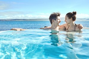 Woman and man relaxing in pool outside