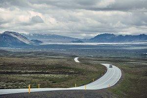 plot of asphalt road in a bright sunny mountain landscape