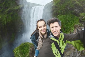 smiling happy couple making selfie on a Skogafoss waterfall background