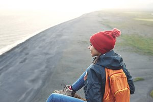 woman hiker with backpack standing on top of a mountain and enjoying sunset in Iceland