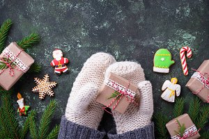 Hands in mittens holding Christmas gift box