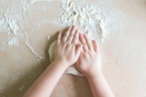 Children's hands make dough