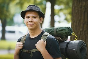 Portrait of a young man tourists in hat with backpack outdoor