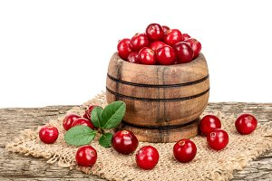 Cranberry with leaf in wooden bowl on old wooden table with white background