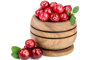 Cranberry with leaf in wooden bowl isolated on white background closeup