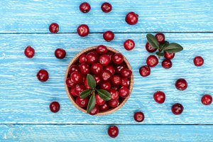 Cranberry with leaf in bowl on blue wooden background. Top view