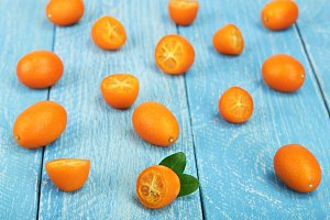 Cumquat or kumquat with half on blue wooden background