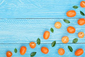 Cumquat or kumquat with leaf on blue wooden background with copy space for your text. Top view. Flat lay pattern