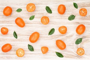Cumquat or kumquat with leaf on white wooden background. Top view. Flat lay pattern