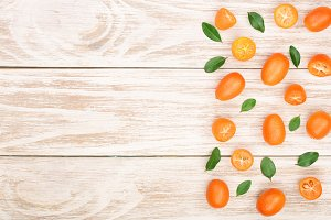 Cumquat or kumquat with leaf on white wooden background with copy space for your text. Top view. Flat lay pattern