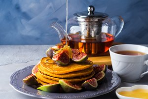 Stack of pumpkin pancakes with figs and honey