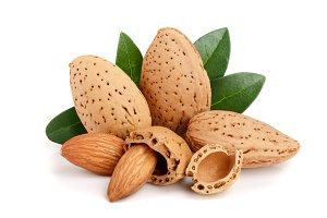 Group of almond nuts with leaves isolated on white background
