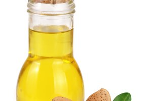 Bottle of almond oil and almonds with leaves isolated on white background