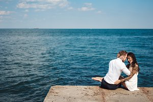 Young couple are sitting on the pier by the sea