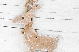 Decorative wooden reindeer on snow