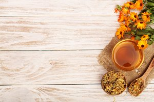 Calendula tea with fresh and dried flowers on white wooden background with copy space for your text. Top view