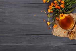 Calendula tea with fresh and dried flowers on black wooden background with copy space for your text. Top view