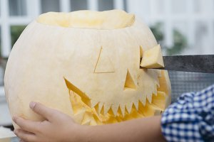 Little girl carving pumpkin