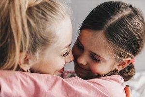 A little daughter hugs her mother
