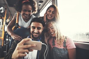 Smiling group of friends listening to music on a bus