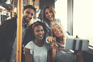 Smiling friends taking selfies together on a bus