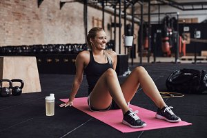 Smiling woman sitting on a gym floor after working out