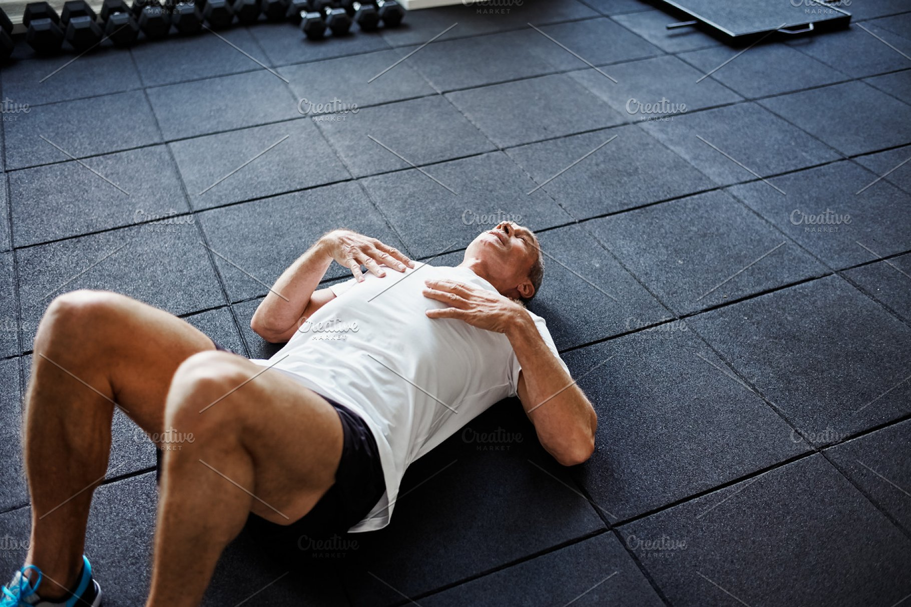 Exhausted man lying on a gym floor