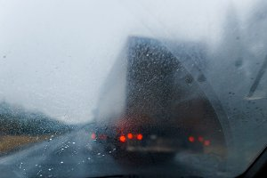 Rain drops on windscreen and blurred truck in forest road. Overtaking of the truck. Low visibility.