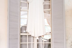 A white bridal dress on wooden shoulders, against the window. Artwork