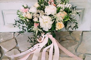 Rustic wedding bouquet with creamy roses, white carnations, and eustoma stand on the floor. Close-up.