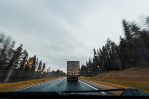 Arkhangesk, Russia - 11 october 2017: Truck on Autumn forest road at high speed drive. View of windscreen
