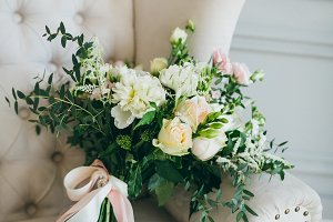 Rustic wedding bouquet and rings in the black box on a luxury sofa. Indoors. Artwork